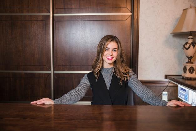 Portrait dune jeune réceptionniste sympathique debout à son bureau