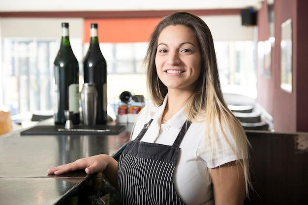Portrait de jeune serveuse souriante au bar Photo gratuit