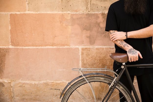 Portrait, jeune, tatouage, debout, main, vélo, mur Photo gratuit
