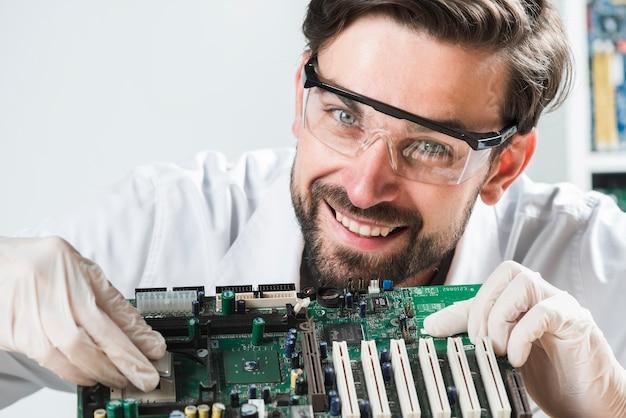 Portrait, de, a, jeune technicien mâle, insérer, puce, dans, carte mère ordinateur Photo gratuit