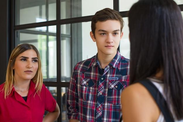 Portrait de jeunes amis étudiants confiants parler à la pause Photo gratuit