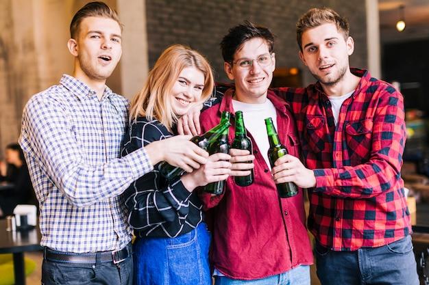 Portrait de jeunes amis souriants tinter les bouteilles de bière verte Photo gratuit