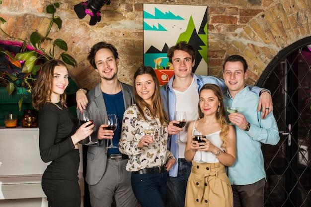Portrait de jeunes amis tenant des verres de boissons en boîte de nuit Photo gratuit