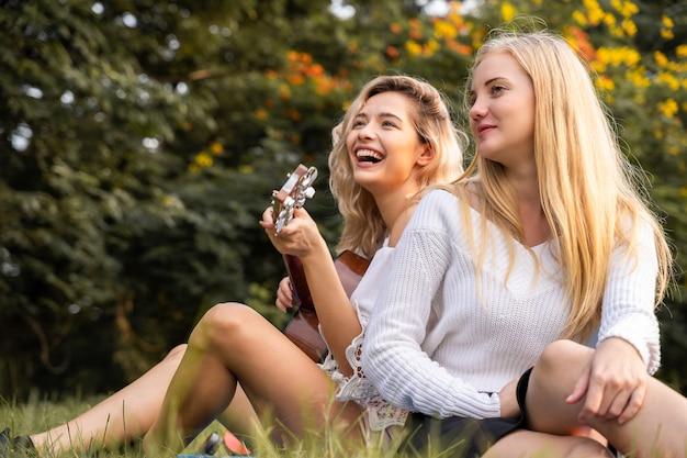 Portrait De Jeunes Femmes De Race Blanche Assis Dans Le Parc En Plein Air Et Jouer De La Guitare Chanter Une Chanson Avec Bonheur Photo Premium