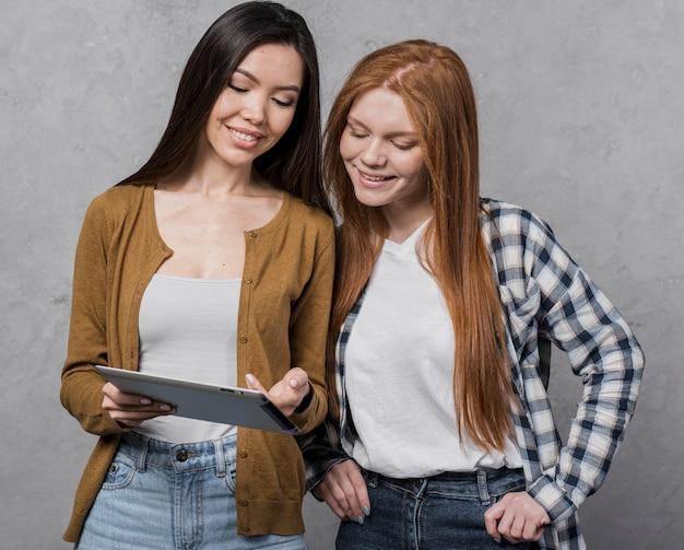 Portrait De Jeunes Femmes à La Recherche Sur Une Tablette Photo gratuit