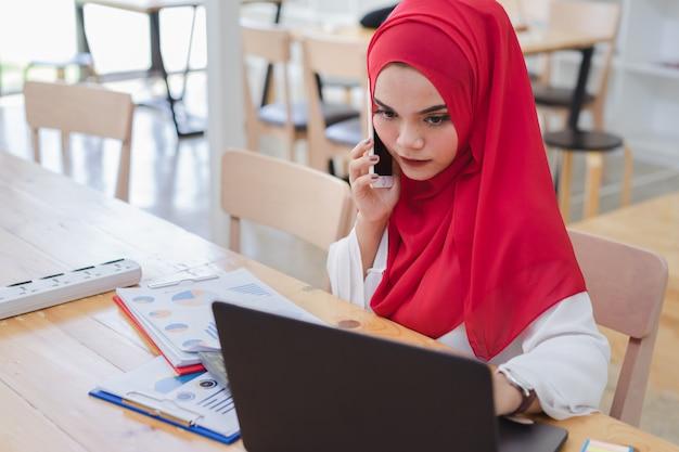 Portrait de jeunes gens d'affaires musulmans portant le hijab rouge, travaillant au café. Photo Premium