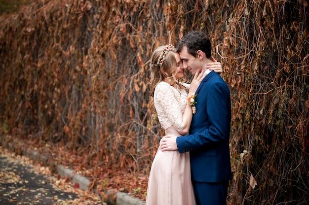 Portrait de jeunes mariés heureux dans la nature en automne. Photo Premium