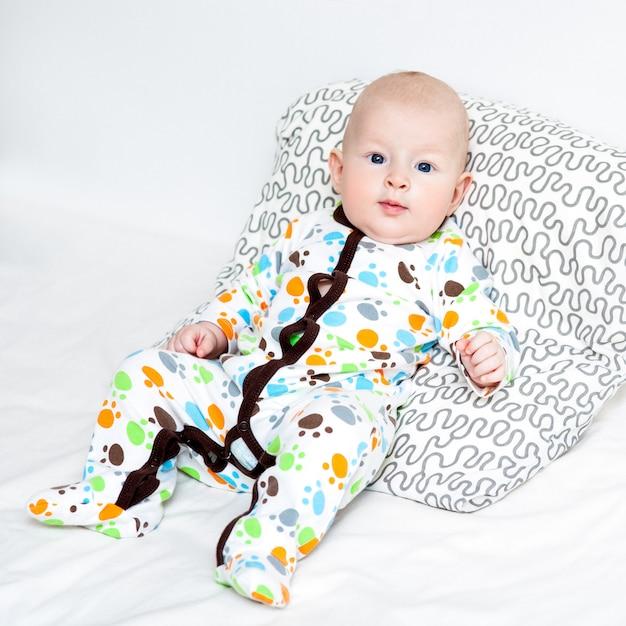 Portrait d'un joli bébé couché sur un lit, vue de dessus. Photo Premium