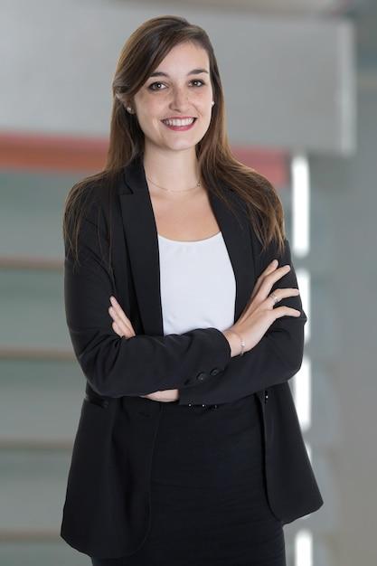 Portrait de jolie femme d'affaires avec les bras croisés sur le bureau gris Photo Premium