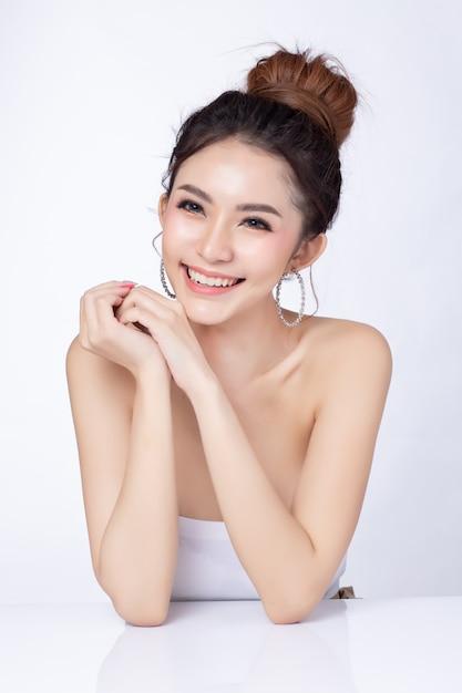 Portrait de jolie femme asiatique assise souriant sur fond blanc. Photo Premium