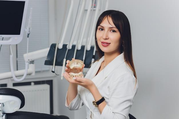 Portrait De Jolie Femme Dentiste Souriante Avec Les Mains Jointes. Photo Premium