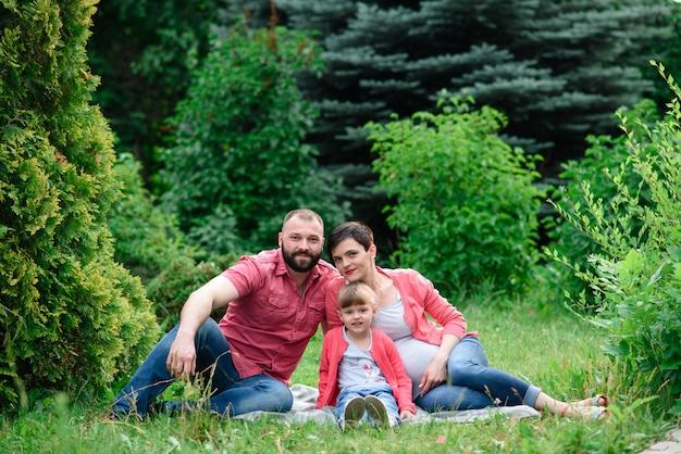 Portrait de jolie femme enceinte avec son jeune mari et son petit enfant mignon embrassant et marchant dans le parc. Photo Premium