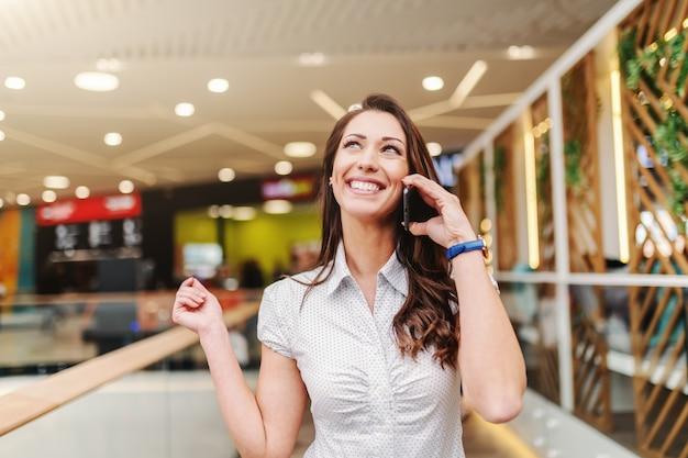 Portrait De Jolie Femme De Race Blanche Aux Longs Cheveux Bruns Habillé Décontracté à L'aide De Téléphone Intelligent Dans Le Centre Commercial. Photo Premium
