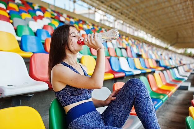 Portrait d'une jolie femme en vêtements de sport assis et buvant de l'eau dans le stade. Photo Premium