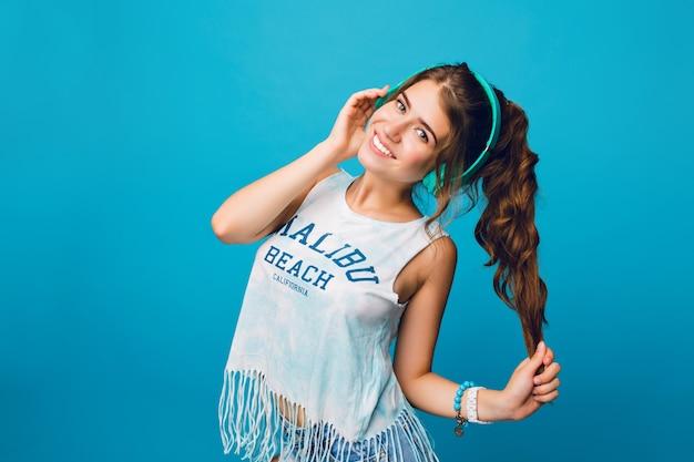 Portrait De Jolie Fille Aux Longs Cheveux Bouclés En Queue Sur Fond Bleu. Elle Porte Un T-shirt Blanc, Un Short Et écoute De La Musique Avec Des écouteurs Bleus. Photo gratuit