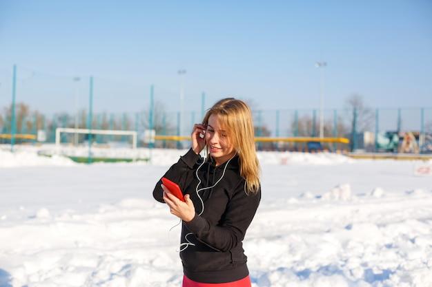 Portrait d'une jolie fille blonde, écoutant de la musique tout en marchant dans la rue, tenant un téléphone rouge à la main. Photo Premium