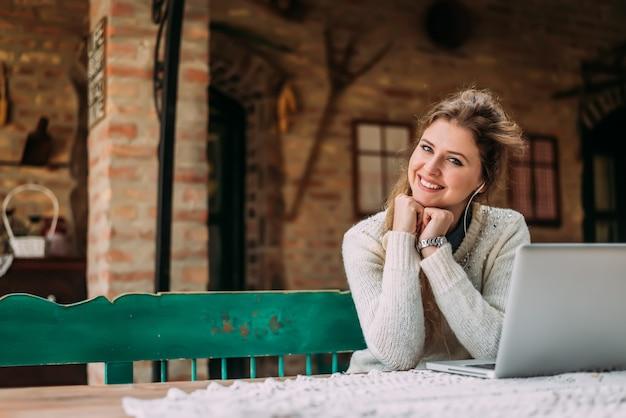 Portrait d'une jolie fille avec des écouteurs et un ordinateur portable au chalet de campagne. Photo Premium