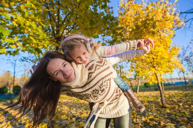 Portrait de jolie fille et heureuse mère s'amuser dans la forêt d'automne jaune par une chaude journée ensoleillée Photo Premium