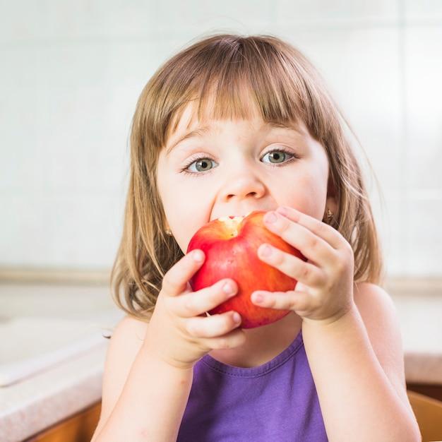Portrait d'une jolie fille en train de manger une pomme rouge mûre Photo gratuit