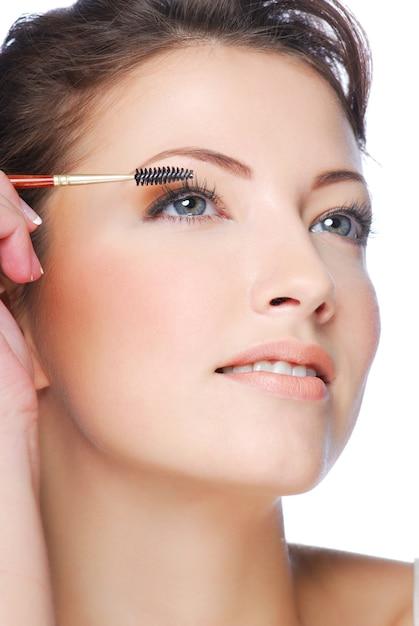 Portrait De Jolie Jeune Femme Appliquant Le Mascara à L'aide D'une Brosse à Cils Photo gratuit