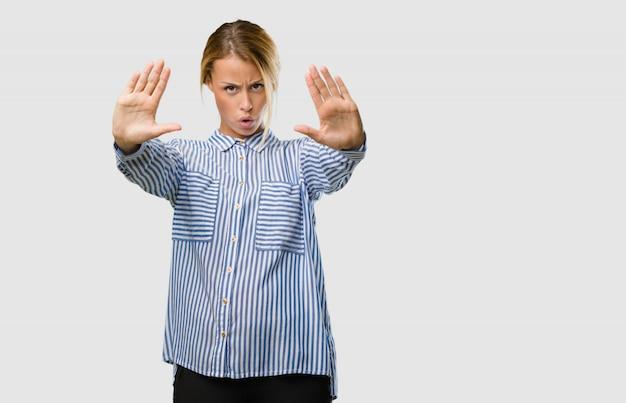 Portrait d'une jolie jeune femme blonde sérieuse et déterminée, mettant la main devant, arrêtez le geste Photo Premium