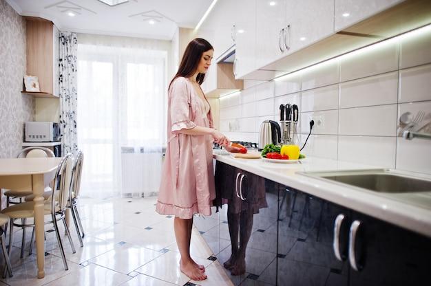 Portrait d'une jolie jeune femme en robe faisant la salade de légumes dans la cuisine. Photo Premium