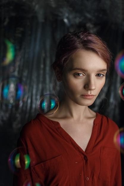 Portrait de jolie jeune fille caucasienne en chemise rouge. des bulles de savon volent autour de sa tête, chatoyantes aux couleurs de l'arc-en-ciel. Photo Premium