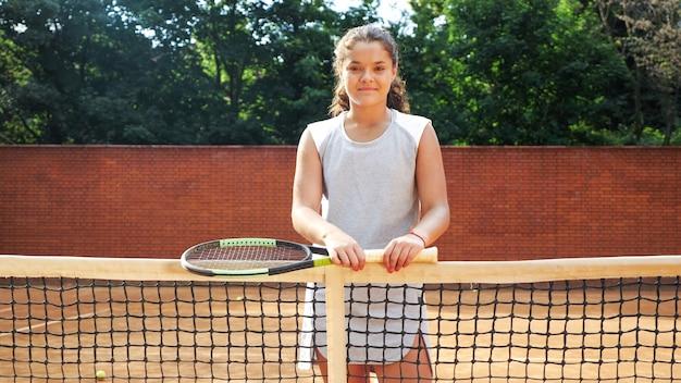 Portrait De Jolie Jeune Playgirl Tennis Debout Avec Raquette Près De Net Sur Un Court De Tennis En Terre Battue Orange Photo Premium