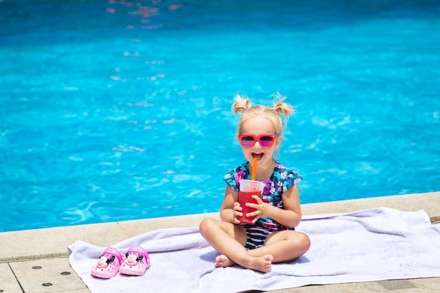 Portrait de jolie petite fille heureuse s'amuser dans la piscine et boire du jus de melon d'eau Photo Premium