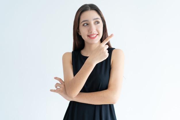 Portrait de joyeuse jeune femme d'affaires indiquant la direction Photo gratuit