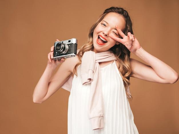 Portrait De Joyeuse Jeune Femme Prenant Des Photos Avec Inspiration Et Portant Une Robe Blanche. Fille Tenant Un Appareil Photo Rétro. Modèle Posant Photo gratuit