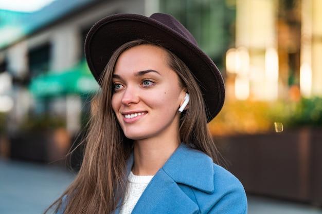 Portrait De Joyeuse Joyeuse élégante Mode Hipster à La Mode Fille Au Chapeau Avec Un Casque Blanc Sans Fil Aime La Musique Dans Le Centre-ville. Mode De Vie Et Technologie Des Peuples Modernes Photo Premium