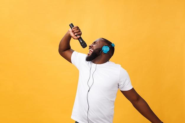 Portrait de joyeux positif bel homme africain beau microphone et avoir des écouteurs Photo Premium