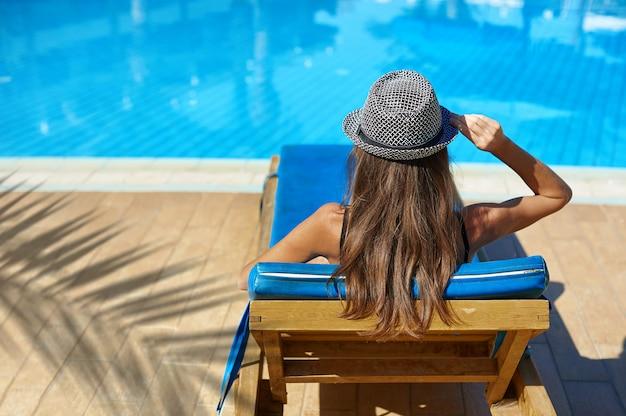 Portrait lifestyle été de jolie jeune femme bronzée avec un chapeau près de la piscine Photo Premium