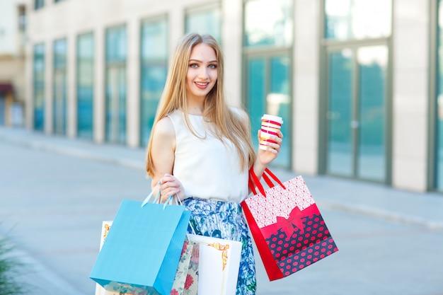 Portrait lifestyle jeune fille blonde, avec des sacs à provisions sortant du magasin. Photo Premium
