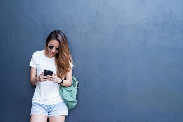 Portrait lifestyle en plein air de jolie jeune fille asiatique sexy dans le style de voyage et de lunettes sur mur gris Photo gratuit