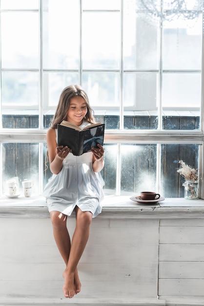 Portrait d'un livre de lecture fille souriante à la maison Photo gratuit