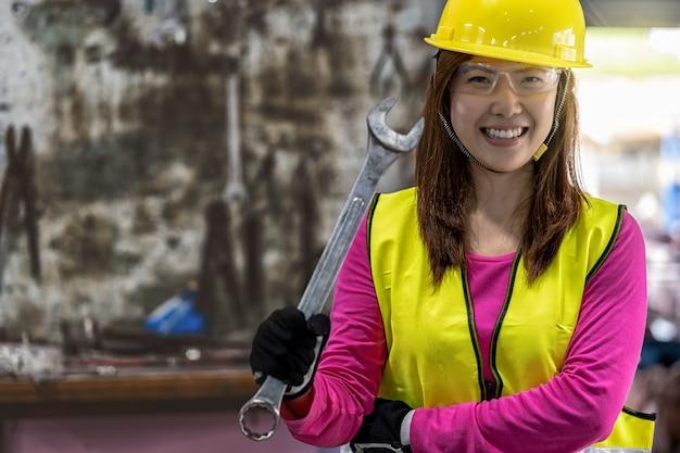 Portrait de machiniste asiatique en combinaison de sécurité tenant la clé sur la pile de clé Photo Premium