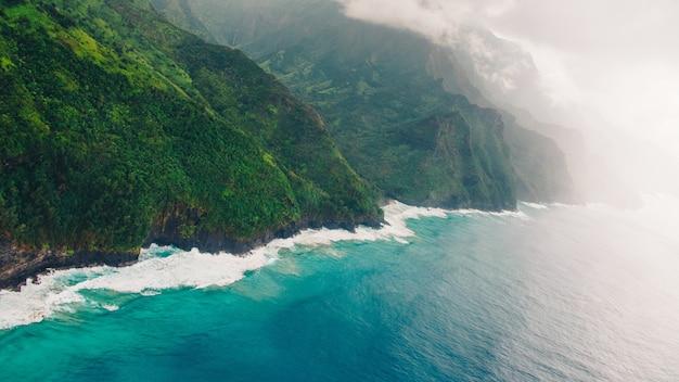 Portrait De La Magnifique Falaise Brumeuse Sur L'océan Bleu Calme Capturé à Kauai, Hawaii Photo gratuit