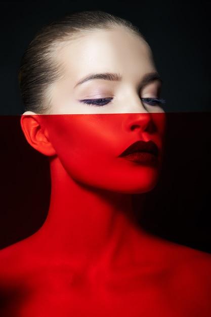 Portrait De Maquillage Beauté Contrastée Lumineux D'une Femme Dans Les Tons D'ombre Bleu Et Rouge. Maquillage Parfait Pour La Peau Et Le Visage, Rouge à Lèvres Foncé Sur Les Lèvres Charnues Photo Premium