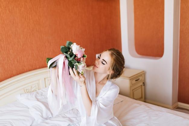 Portrait Mariée Assez Heureuse En Peignoir Blanc Sur Le Lit Le Matin. Elle Regarde Le Bouquet Dans Les Mains Et A L'air Heureuse Photo gratuit