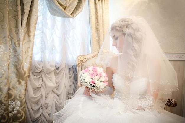 Portrait, mariée, bouquet mariée, roses, main, séance, divan, fenêtre Photo Premium