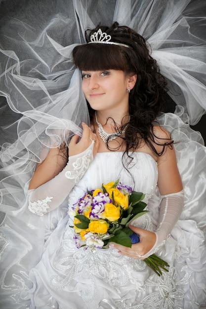 Portrait, mariée, cheveux bouclés, bouquet mariage, roses jaunes Photo Premium
