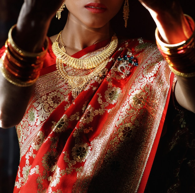 Portrait de mariée hindoue en sari rouge traditionnel avec acce doré Photo gratuit