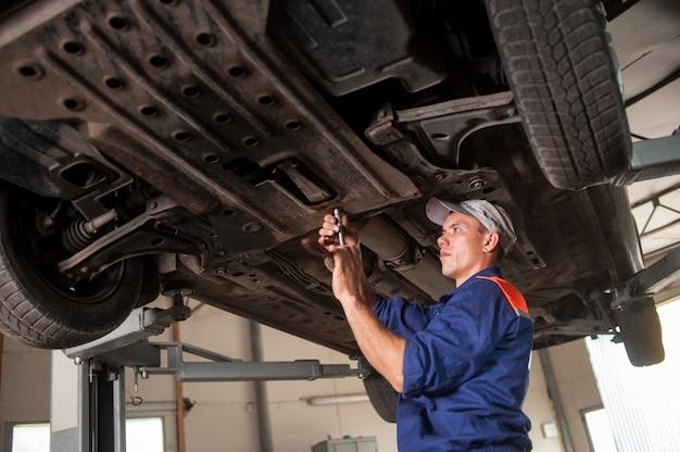 Portrait de mécanicien automobile travaillant avec des outils sous la voiture Photo Premium
