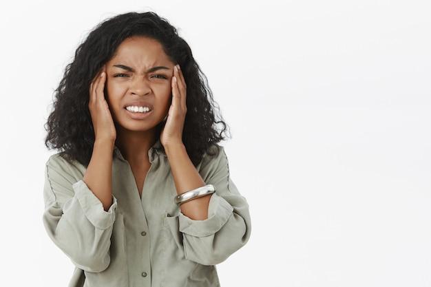 Portrait De Mécontent Intense Jeune Femme Afro-américaine Aux Cheveux Bouclés Fronçant Les Sourcils Serrant Les Dents De Sensation Douloureuse Touchant Les Tempes Photo gratuit