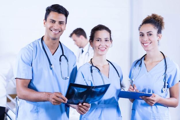 Portrait de médecins tenant un rapport de radiographie et souriant à l'hôpital Photo Premium