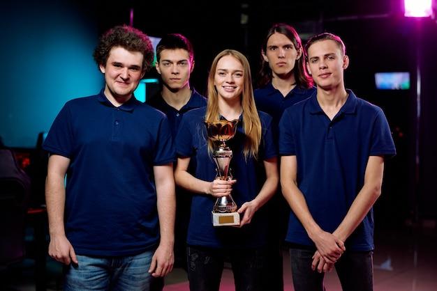 Portrait De La Meilleure équipe De Cybersports Positive En T-shirts Bleus Posant Avec Un Prix Gagnant En Club Informatique Photo Premium