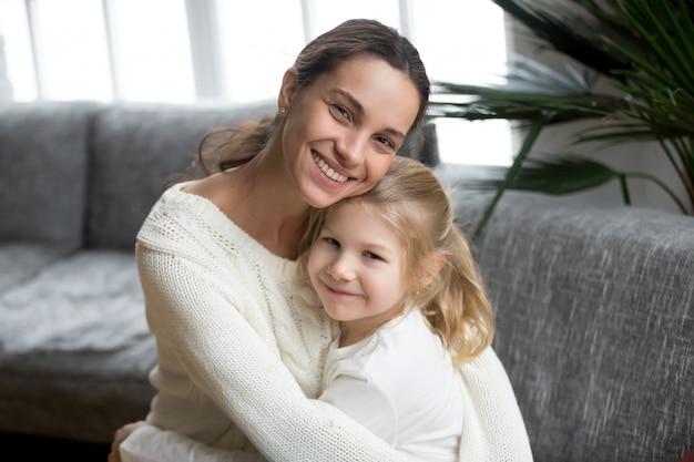 Portrait de mère célibataire aimante étreignant jolie petite fille Photo gratuit