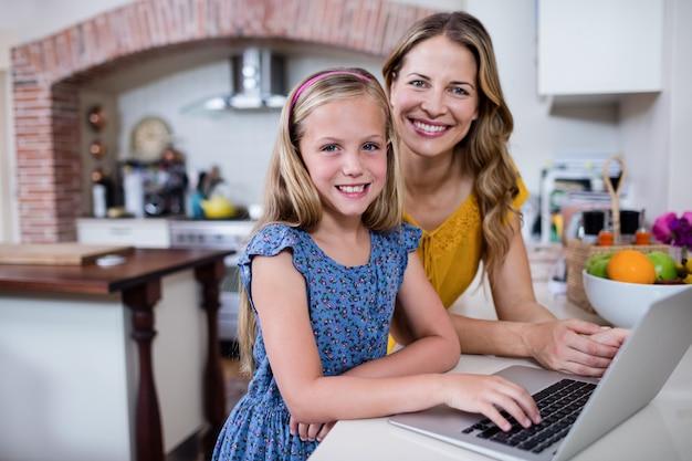 Portrait de mère et fille à l'aide d'un ordinateur portable dans la cuisine Photo Premium